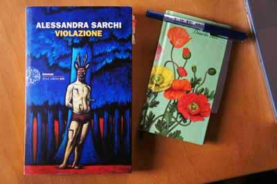 """Il romanzo """"Violazione"""" sulla scrivania con taccuino"""